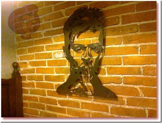 Foto da estrutura em ferro do cantor David Bowie de autoria o escultor Rui Miragaia, pendurada numa parede da loja de café Fábrica - Coffee Roasters