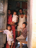 A village family in the doorway to their home