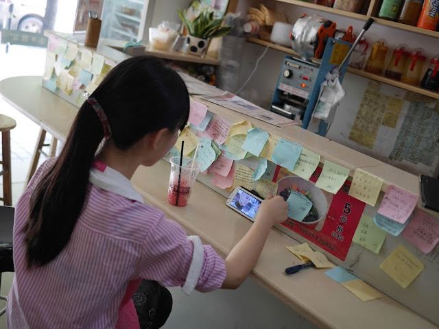 girl viewing Chinese video on a mobile phone and many colored notes with messages on them at the Black Tide (黑潮) cafe