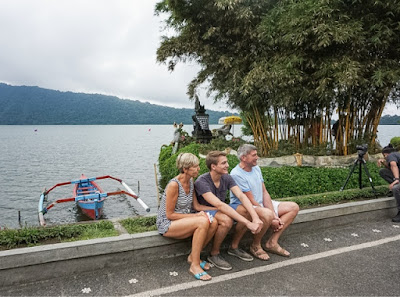 Turis asing berfoto dengan latar danau dan pura ulun danu.