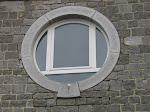 9 - Gefrijnd en in het midden gebouchardeerd rond raam