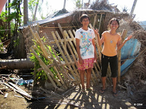 Two women in front of a ruined house.