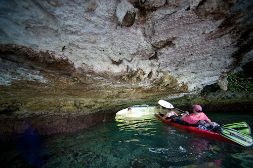 photo of people paddling under a rock in a kayak
