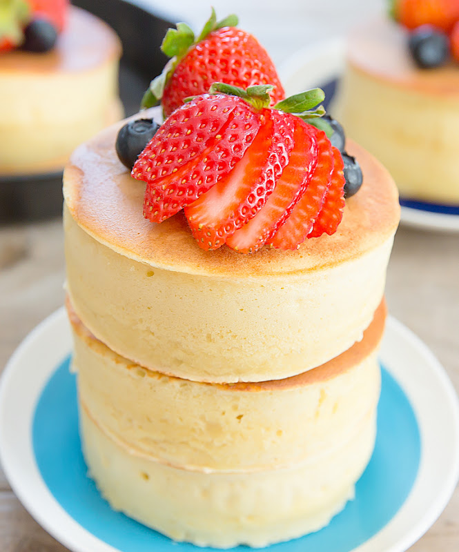 a close-up photo of two Japanese-style pancakes stacked on top of each other with fresh fruit