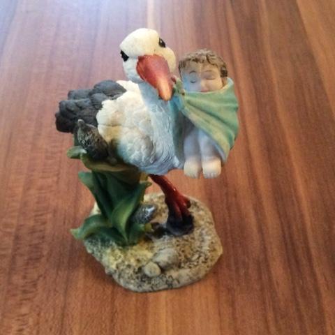 Storch mit Baby im Schnabel