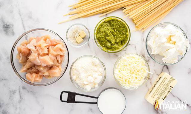 pesto chicken pasta ingredients on a marble board
