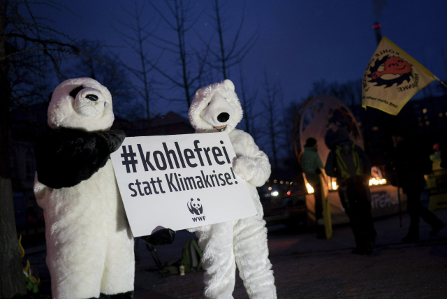 Protesters dressed as polar bears hold a poster prior to a meeting of a panel of experts on the exit of the using coal in Germany called 'Coal Commission' in Berlin, Germany, Friday, 25 January 2019. Germany wants to stop using coal, a major source of the carbon emissions that drive climate change. The slogan reads 'coal free - instead of climate crises'. Photo: Kay Nietfeld / dpa / AP