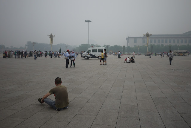 man sitting and a police van at Tiananmen Square