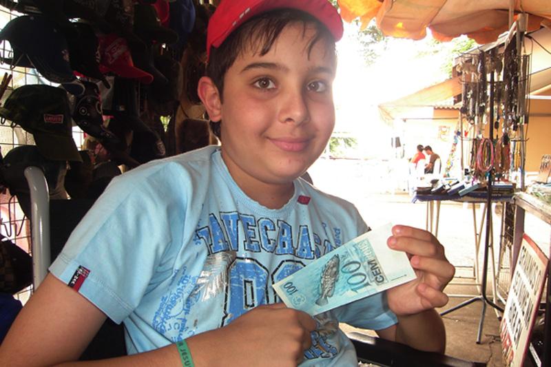 Vitor mostrando a nota de R$ 100,00 que usou para comprar o quadro do peixe