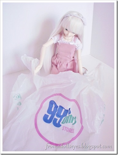 A ball jointed doll peeking in a 99 Cents Only Store shopping bag to see what's inside.