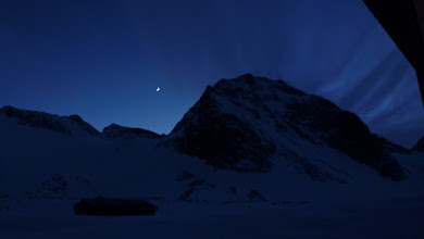 Photo: The Moon and a hairy mountain. My best guess is that wind is blowing snow over the mountain and creating an illusion of hair.