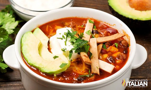 easy taco soup in a white soup crock with avocado on top