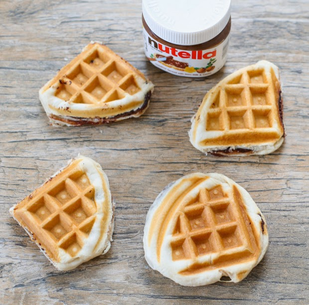 top-down photo of four small Nutella-stuffed waffles with a jar of nutella