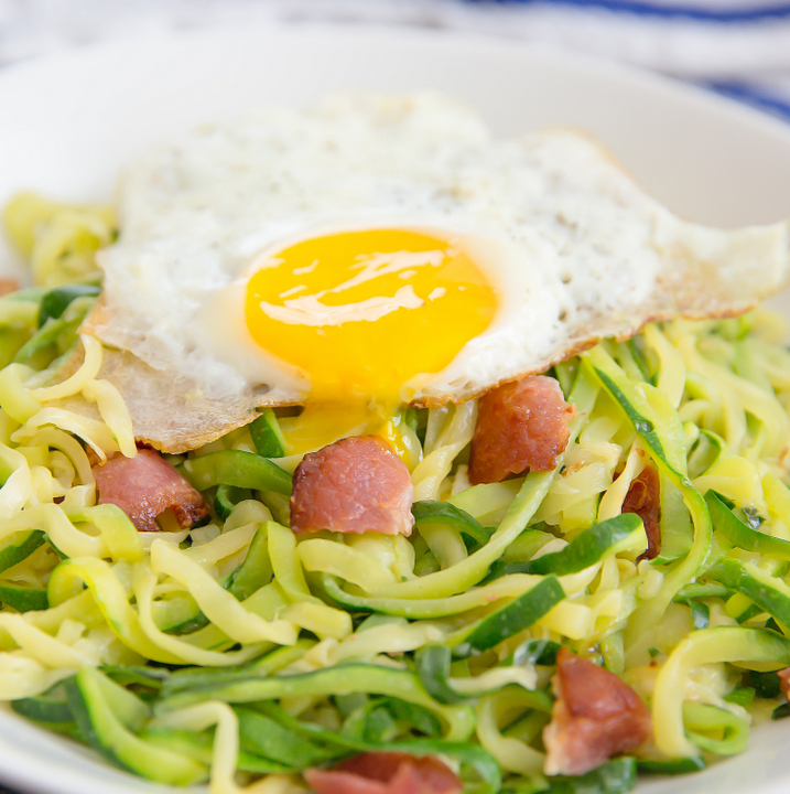 close-up photo of zucchini noodles carbonara with a fried egg