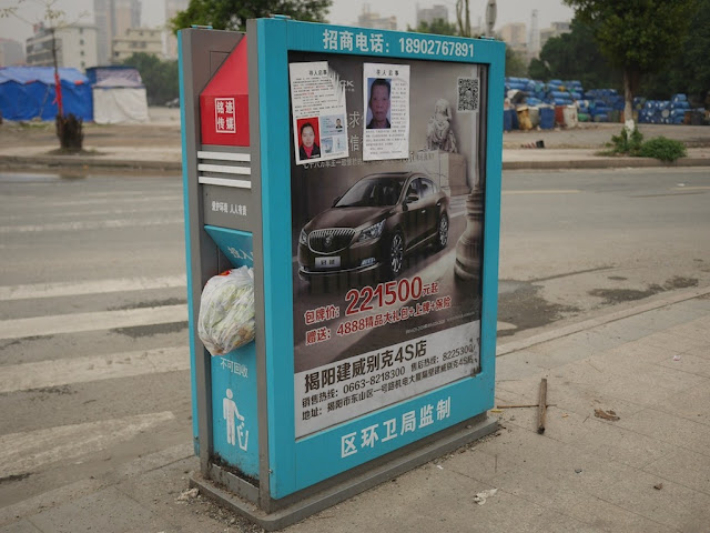 missing person signs on top of an automobile advertisement in Jieyang, China