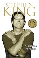 """Portada del libro """"Mientras escribo"""", de Stephen King. Aparece el autor en la portada, con los brazos cruzados sobre el pecho y las palmas sobre el hombro contrario, en tono monocromático."""