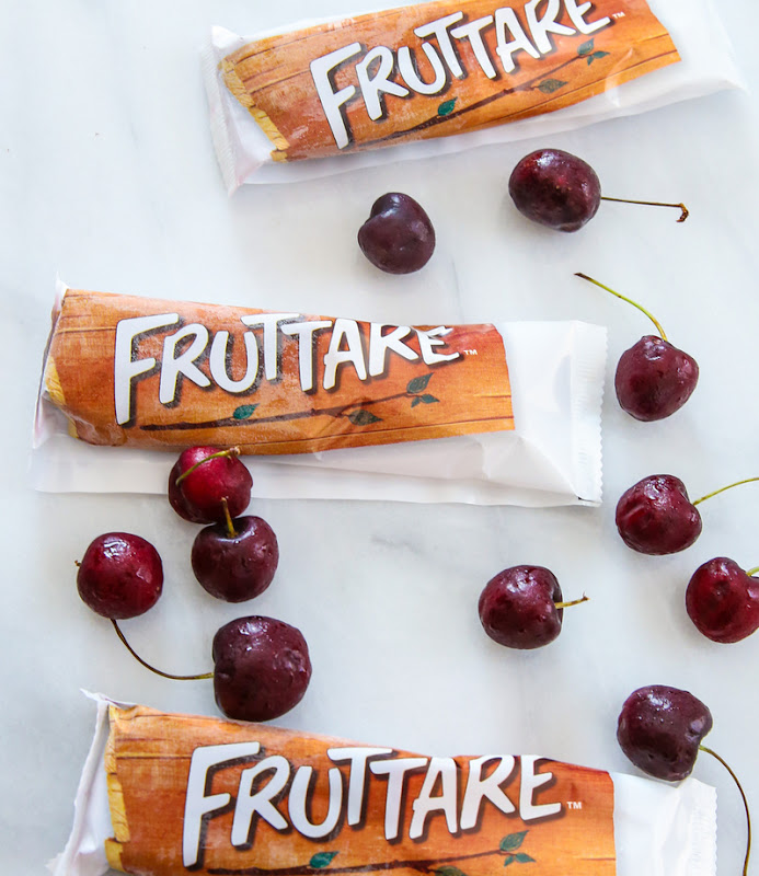overhead photo of three packages of Fruttare ice bars with fresh cherries scattered around