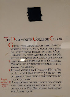 A page printed with black and red text. A square of fabric is affixed to the page.