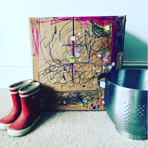 a cardboard box rocket, moon boots and space helmet