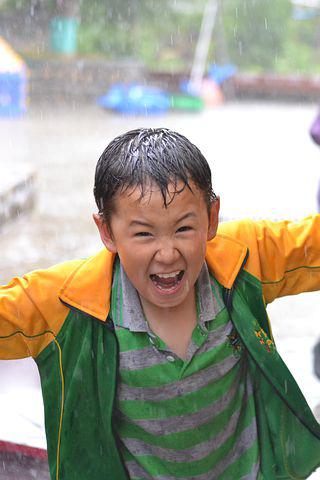 Anak-anak bergembira saat  bermain hujan