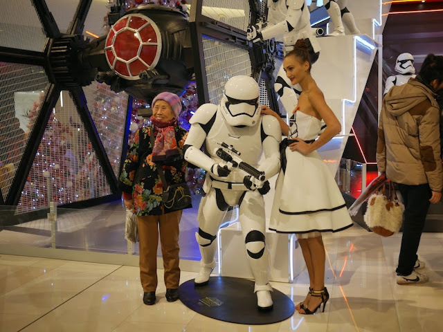elderly woman posing for a photograph with a female Star Wars model and a Stormtrooper at the IAPM shopping center in Shanghai