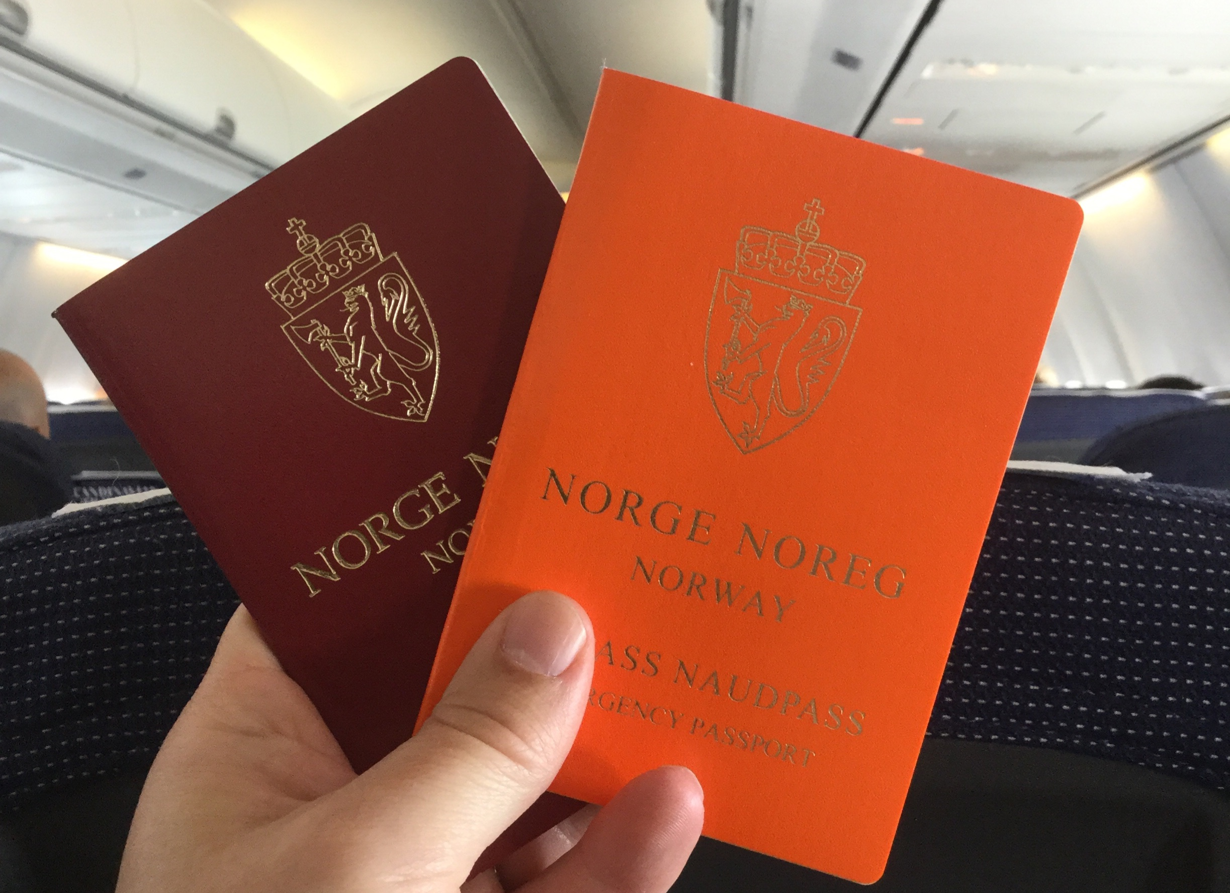 Et rødt og et oransje pass i flykabinen