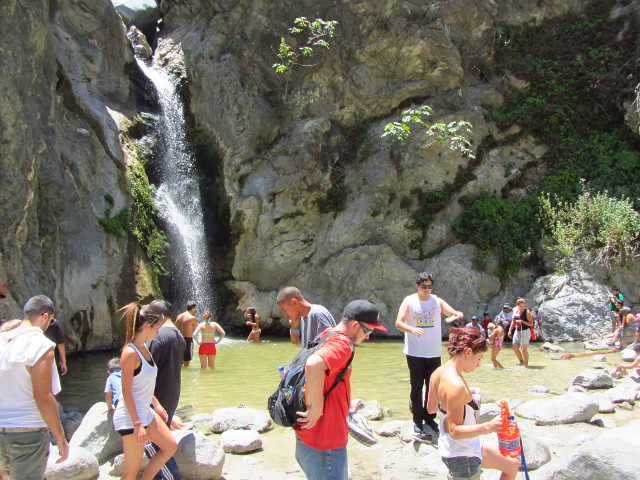 more crowds directly around the waterfall pool