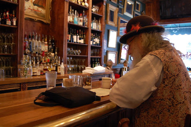 Dirty Dan Harris (portrayed by Jim Roth) enjoys his book at the bar in Skylark's Hidden Cafe in Fairhaven.  Credit: Bellingham Whatcom County Tourism