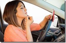 Donna alla guida con lo smartphone