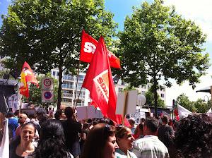 Demonstrantinnen und Demonstranten mit Fahnen und Transparenten.