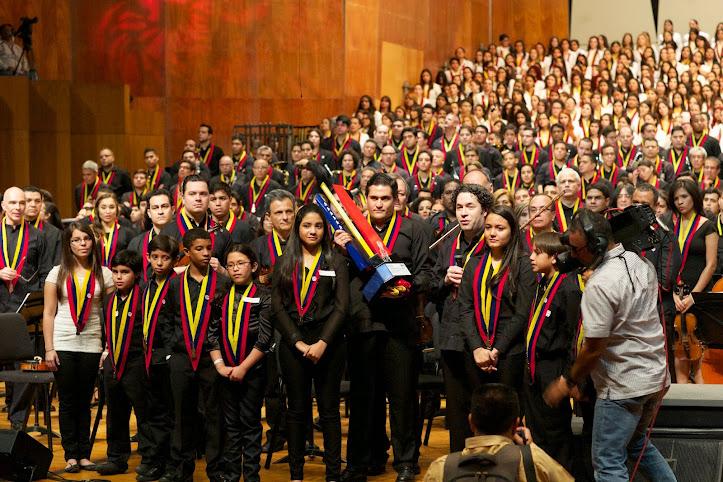 Eduardo Méndez, director ejecutivo de Fundamusical Bolívar, y el maestro Dudamel, acompañados de una delegación de niños y jóvenes de la Sinfónica Nacional Infantil de Venezuela, entregan un reconocimiento al maestro Abreu