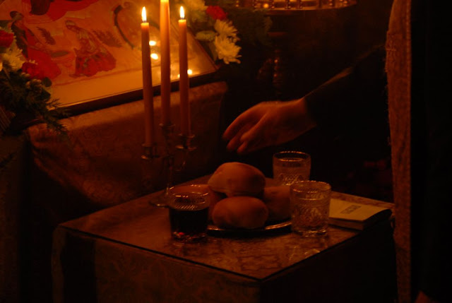 Fr. John blesses the loaves, wheat, wine, and oil during the vigil on Christmas Eve.