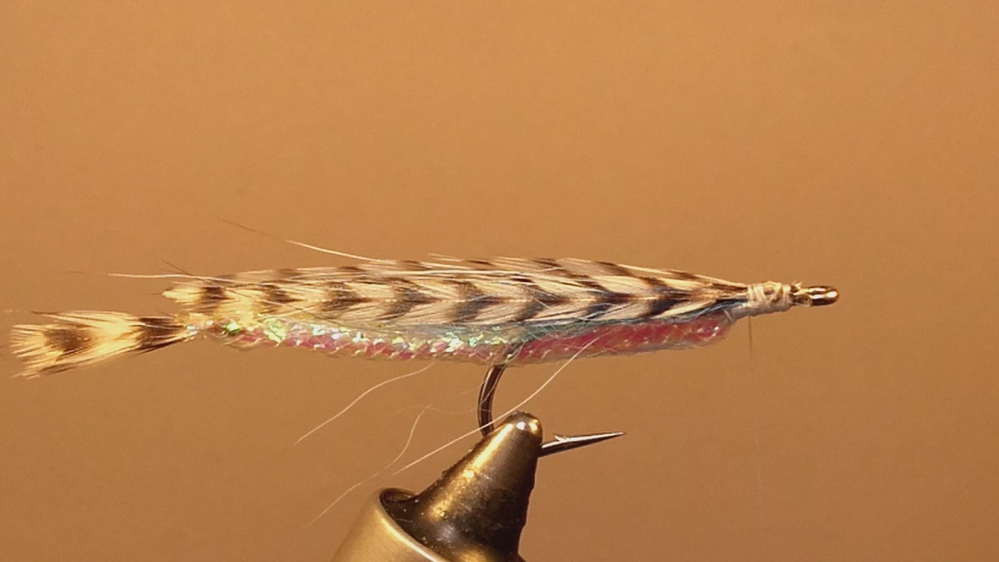 5. Na pęczku włosia układam w daszek parę piór szyjnych koguta grizzly - powinny sięgać do końca mylaru.