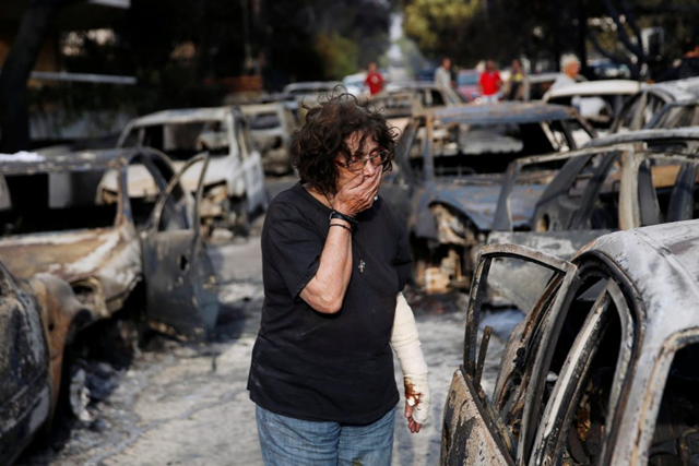 A woman reacts as she tries to find her dog among burned-out cars, following a wildfire at the village of Mati, near Athens, Greece, 24 July 2018. Photo: Costas Baltas / Reuters