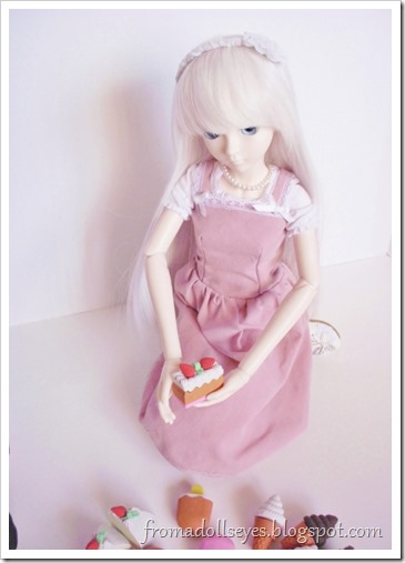The first ball jointed doll holding a strawberry cake shaped food eraser.