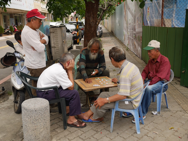 men playing and watching a game of banqi outside in Tainan, Taiwan