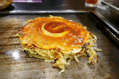 Dinner of okonomiyaki in Namba, Osaka at Ajinoya. This is the Hiroshima styled okonomiyaki which you can then top with as much additional sauce and bonito flakes as you want from containers on the table