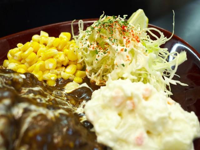 皿の脇に盛られたコーンマヨ、キャベツ千切り、ポテサラ