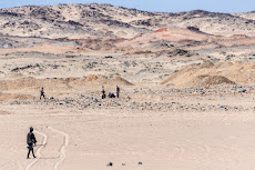 People walking around in the desert and searching for gold.