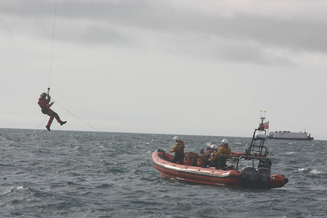 9 October 2011. Poole inshore lifeboat (ILB) prepares to receive  the winchman from Portland Coastguard helicopter 106 during a training exercise. Photo: Poole RNLI/Ade.