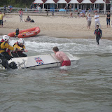 1 September 2012 - crew members and a member of the public attempt to right the upturned motorboat. Photo credit: Poole RNLI/Dave Riley