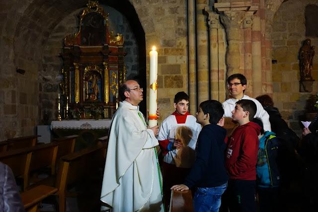 El párroco sostiene el Cirio Pascual mientras el sacerdote que concelebraba, niños y monaguillos observan