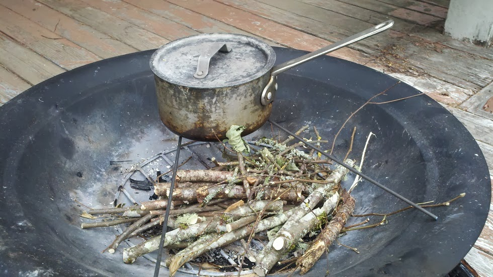 Cooking with a pot over a fire pit