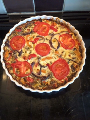 a crustless quiche in flan dish on top of a cooker. Cooked with a herby tomato top.