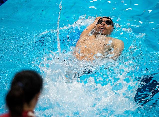 Daniel Dias nada de costas no centro da raia usando sunga, óculos e touca pretos