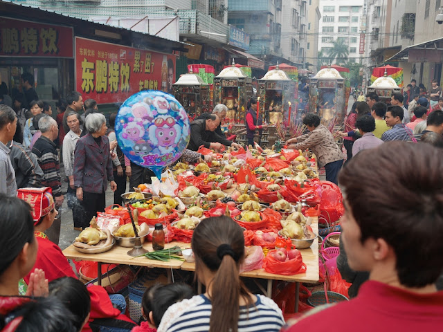god figures facing a table of food during the Nian Li Festival (年例节) in Maoming, China