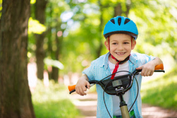 Boy riding bike and smiling