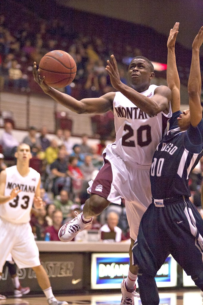 Keron DeShields (#20) powers past San Diego's point guard Chris Anderson, as forward Michael Weisner stands ready for the dump-off.  Dahlberg Arena in Missoula, Mont., November 24th, 2012. Photo by Austin Smith.