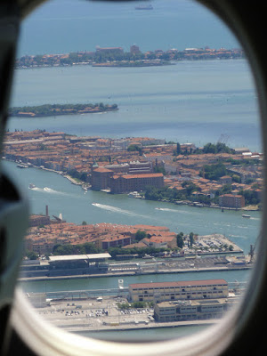 Utsikt mot en by på noen øyer gjennom et flyvindu.
