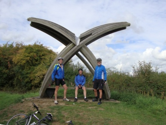 3 members in front of a sculpture